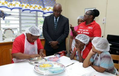 Happy Haven camp attendee Rachel Jemmott prepares a special sandwich for Chief Secretary Kelvin Charles who watches along with Principal Dianne Le Cointe.