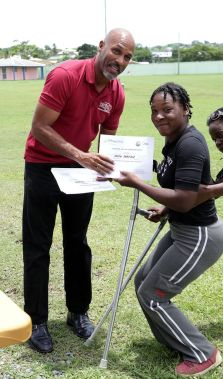 Secretary for Sport Jomo Pitt presents participant Faith Farfan with her certificate of participation during the programme led by Play Able Caribbean.
