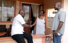 THA Chief Secretary Kelvin Charles and Secretary of Settlements, Urban Renewal and Public Utilities Clarence Jacob greet homeowner Grace McKenzie.