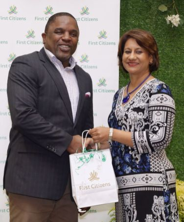 Tobago House of Assembly Deputy Chief Secretary Joel Jack, who is also the Secretary for Finance and the Economy Joel Jack receives a gift from First Citizens group chief executive officer Karen Darbasie.