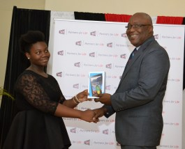 Shenicka Collete receives her award from THA Chief Secretary Kelvin Charles.