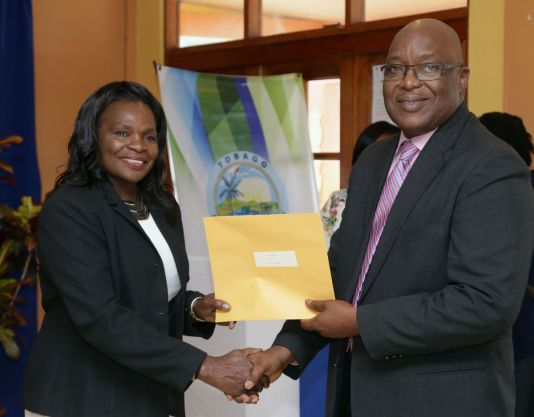 Shirley Cooke receives her instrument of appointment from THA Chief Secretary Kelvin Charles.