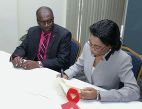 Acting Permanent Secretary in the Ministry of Labour and Small Enterprise Development Natalie Willis, right, signs the Memorandum of Understanding on the National workplace Police on HIV and AIDS with THA Chief Administrator Raye Sandy.