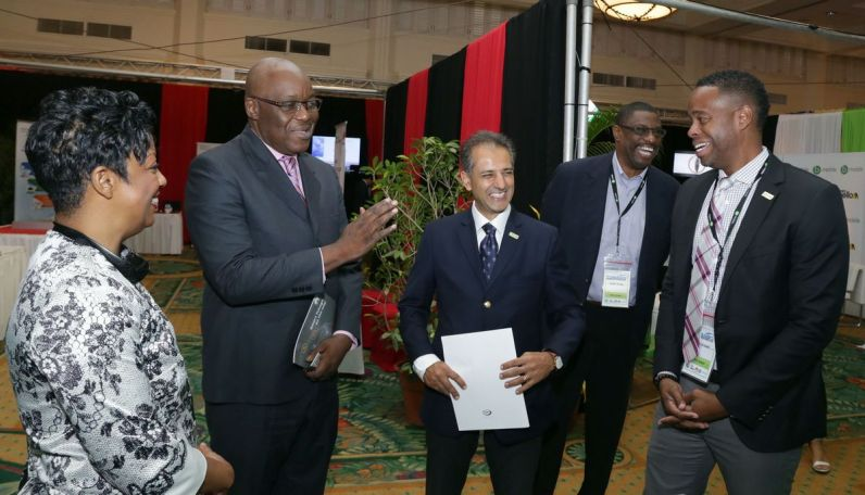 Chief Secretary Kelvin Charles, second from left, shares a light moment with TSTT representatives, from left, senior mManager (Tobago) Frances Simmons,executive vice-president strategic alliance, enterprise and Tobago operations Rakesh Goswami, senior manager enterprise marketing Ralph Young and senior manager government, security and other business, Darryl Duke, at their display booth.