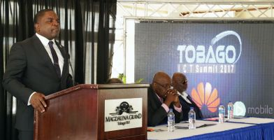 Secretary of Finance Joel Jack addresses the opening of the ICT Summit at the Magdalena Grand Beach Resort on Tuesday. At the head table are, from left, Chief Secretary Kelvin Charles and TITL chairman Dr John Prince.