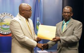 Micheson Neptune, deputy chairman, receives his instrument of appointment.