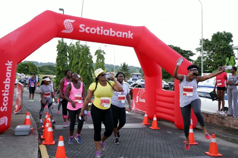 A participant jumps in celebration as she crosses the finish line of the 5K.