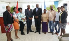 New homeowners stand with Chief Secretary Kelvin Charles, fourth from left, and Secretary for Settlements, Urban Renewal and Public Utilities Clarence Jacob. Also in photo, from left, are Settlements Division Administrator Denese Toby-Quashie, Natalie Chapman, Charmaine Louis, Carlene Toppin-Duke, Selwyn Archie and his wife Hayley and Director of Settlements Petunia Lewis.