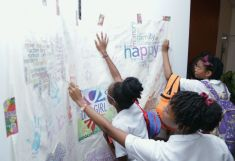 Pupils of Bishop's High School place a palm print and sign a commemorative canvass to mark the Day of the Girl Child.