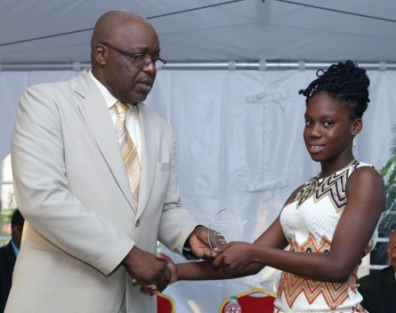 Chief Secretary Kelvin Charles, left, presents Camice Wills with her SEA achievement award.