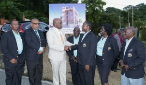 Chief Secretary Kelvin Charles, third from left, congratulates Fire Service Credit Union president Marlon Charles following the ceremony. Also in photo are, from left, FSCU board members Wesley Meade, Ruben Griffith, Garth Jacob, Sharon Nicholson-Charles and Horace Leach.