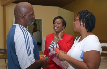 Secretary of Tourism, Culture and Transportation Nadine Stewart-Phillips, centre has a chat with attendees after the meeting.