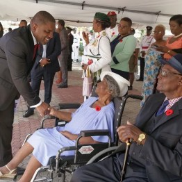 Deputy Chief Secretary Joel Jack greets Tobago's last surviving paid of World War II veterans Lucille Dennis-Cooke, 94, and Eman Legall, 91, during the Remembrance Day celebration.