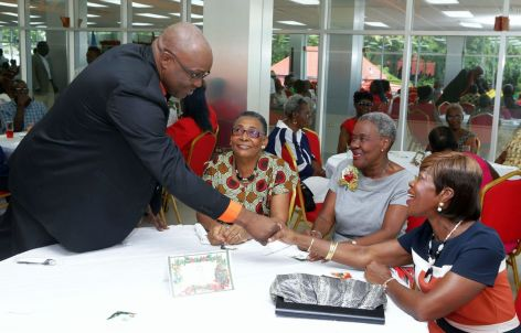 THA Chief Secretary Kelvin Charles shakes the hand of a senior during the luncheon.