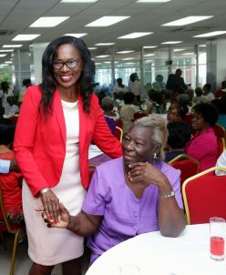 Catherine Charles, wife of Chief Secretary Kelvin Charles, greets guests at the luncheon for senior citizens.
