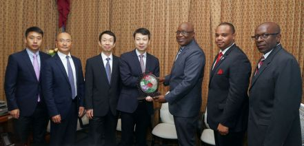 Managing Director Meng Yan presents a gift to Chief Secretary Kelvin Charles. Standing from left are Marketing and Commercial Manager Junqiang Li, Deputy General Manager Dongsheng Li and Director Wenhua Han.