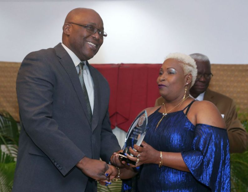 Chief Secretary Kelvin Charles receives a token of appreciation from NUGFW General Secretary Gillian Joy Bartlett-Alleyne.