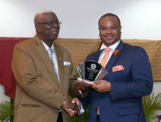 Secretary of Infrastructure, Quarries and the Environment Kwesi Des Vignes receives an award on behalf of his Division, which was selected as 'Division of the Year 2017' from NUGFW President General James Lambert.