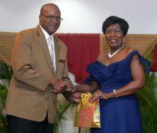 Secretary of Community Development, Enterprise Development and Labour Marslyn Melville-Jack receives a token from Second Deputy President General Clifton Simpson.