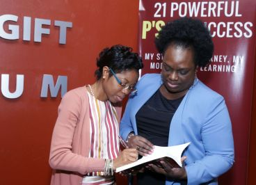 Nichola Harvey-Mitchell autographs her book for President of the Industrial Court Deborah Thomas-Felix who attended the book launch at the Anne Mitchell Gift Auditorium.