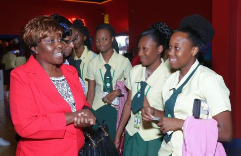 Assistant Secretary in the Division of Education, Innovation, and Energy Marisha Osmond, left and the Administrator in the Division Jacqueline Job, second from left, chat with Signal Hill Secondary school pupils (from left) Afiah Muir, Kaylan Edwards and Avonelle Loraine prior to the start of the movie.