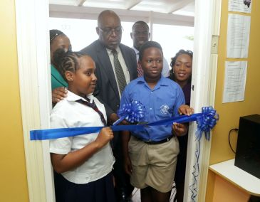 Chief Secretary Kelvin Charles cuts the ribbon to symbolically reopen the Community Y-Zone at Calder Hall as Scarborough Methodist Primary school students Kadiya Shanghie, left, and Shamol Moore look on. Also in photo from left are Administrator in the Division of Community Development, Enterprise Development and Labour Cheryl Ann Solomon, Assistant Secretary Shomari Hector and Community Development Coordinator Michelle Burris.