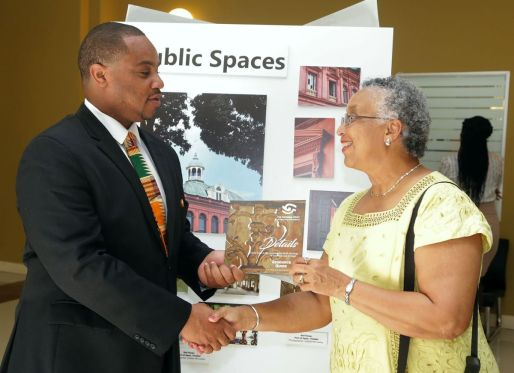 """Secretary of Infrastructure, Quarries and the Environment Kwesi Des Vignes receives a copy of the resource guide produced by the National Trust from Chairman of the Trust Margaret McDowall. The guide was produced as part of the """"Details"""" photographic exhibition which was opened at the Scarborough Library Facility on Monday (March 5, 2018)."""
