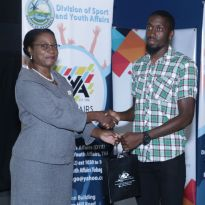 Administrator in the Division of Sport and Youth Affairs Wendy Guy-Hernandez presents goat racing jockey Shaquille Harris with a token of appreciation.