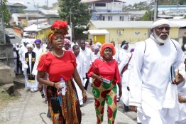 Secretary of Tourism, Culture and Transportation Nadine Stewart-Phillips (left), Asst. Secretary of Education Marisha Osmond (centre) participating in Stations of the Cross procession in Scarborough with the Spiritual Baptists.