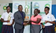 bpTT community sustainability and stakeholder relations adviser Joel Primus, presents Scarborough Secondary teacher Cherise Hector-Trim, and students Phoebe Warner, left, and Maiah Craig-Charles, right, with the trophy for the Inter-schools knockout trophy.