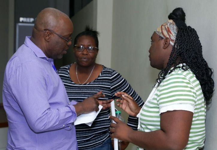 Chief Secretary Kelvin Charles makes a point during a discussion with these residents.
