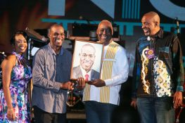 Chief Secretary Kelvin Charles, second from right, presents Tobago-born arranger Duvone Stewart with a framed portrait of himself, done by talented young Tobago artist Shonari Richardson. Also in photo are Secretary of Tourism, Culture and Transportation Nadine Stewart-Phillips, left, and George Leacock, right, the chairman of the Tobago Festivals Commission. Stewart led bp Renegades to the 2018 Panorama title for the first time in over two decades.
