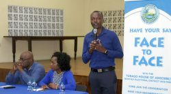 Area Representative Ancil Dennis, right, addresses the community at the beginning of the meeting. At the head table are Chief Secretary Kelvin Charles, left, and public affairs specialist Avian Parks.