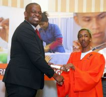 Minister Lovell Francis presents Jude Thom with his graduation certificate.
