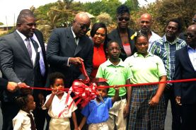 THA Chief Secretary Kelvin Charles cuts the ribbon to mark the official opening of the Lambeau River Bridge. At left is Secretary of the Division of Finance and the Economy Joel Jack, and at right, Minister of Sport and Youth Affairs Shamfa Cudjoe.