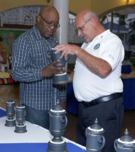 Chief Secretary Kelvin Charles and tournament organiser Jeffrey Azar look at the trophies before they're distributed to winners of the tournament.
