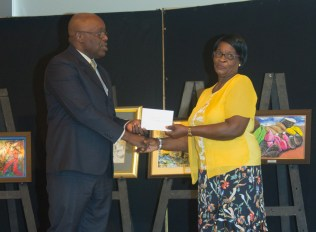 Romelda James, the grandmother of winner Shakir James accepts the prize on his behalf. The younger James is a student of Scarborough Secondary School.