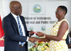 Zaria Baird-St Cyr, right, collects her keys from Chief Secretary Kelvin Charles.