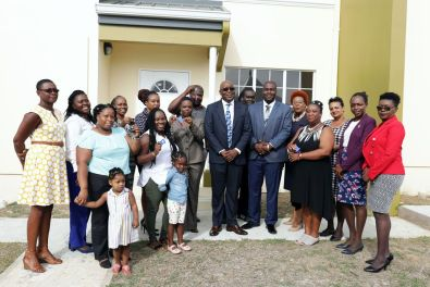 Residents after receiving the keys to their new homes. Also in photo are Chief Secretary Kelvin Charles, centre, to his right Secretary of Settlements, Urban Renewal and Public Utilities Clarence Jacob and Settlements Division Administrator Cherry-Ann Edwards-Louis, and second from left, area representative for Plymouth/Golden Lane, Marisha Osmond.