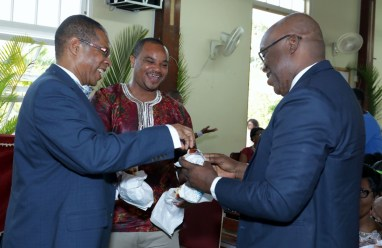 Pathologist Dr. Hughvon Des Vignes, Secretary of Infrastructure, Quarries and the Environment Kwesi Des Vignes and Chief Secretary Kelvin Charles are all smiles as they share a treat.