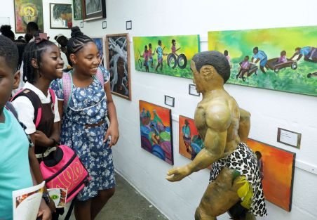 Smiling students admire a work of art.