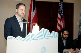The US Embassy's Security Policy and Assistance Coordinator, Jason Hammontree, delivers remarks. At right is Senior Communications Officer in the Ministry of National Security Absalom Yisrael.