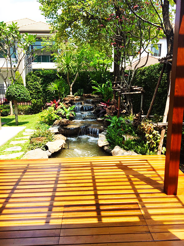 Tropical Rock Waterfall Pond And Shaded Deck In Bangkok