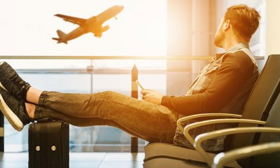 A man sat in an airport with his feet on a suitcase. A place is taking off in the background