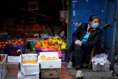 A woman wearing a face mask sits next to a fruit stall at a residential area after the lockdown was lifted in Wuhan, Hubei, 11 April 2020 (Photo: Reuters/Aly Song).