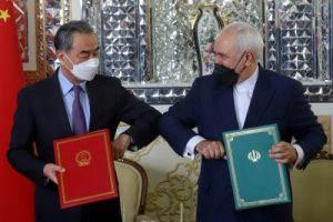 Iran's Foreign Minister Mohammad Javad Zarif and China's Foreign Minister Wang Yi bump elbows during the signing ceremony of a 25-year cooperation agreement in Tehran, Iran, 27 March 2021 (Photo: Reuters/Majid Asgaripour).