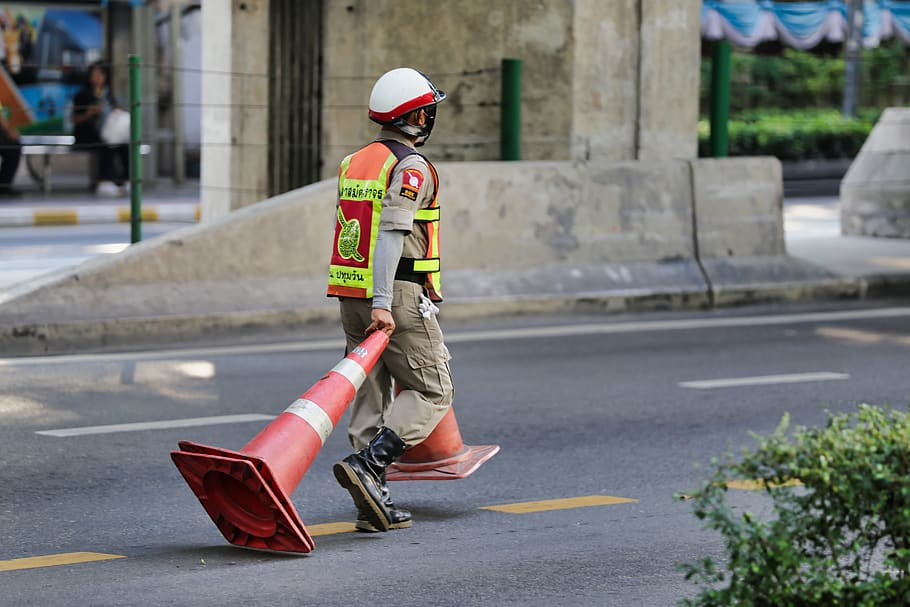Police officer pulling traffic cones along a road in Bangkok