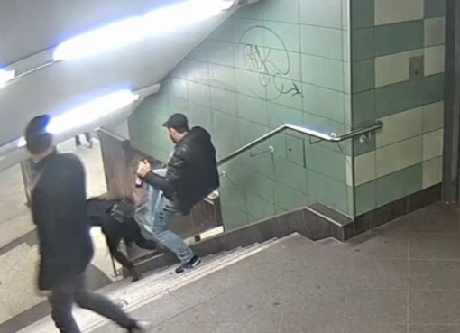 A man kicking a woman stairs down on the Berlin subway