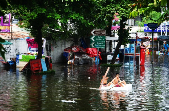 Two boys canoeing during Thai floods