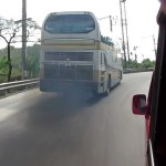 Bus overtaking truck on a curve in Thailand